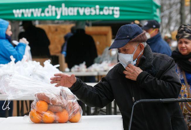 图为在纽约市哈林区,一名男子领取私人食品救援组织「城市丰收」(City Harvest)提供的免费食物。Getty Images