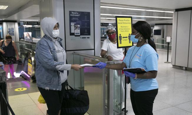 为防病例输入,纽约州市采取强厉措施,在机场、铁路站公路站,都设置检查站,对自外州来的旅客采取实名登记追踪。图为在曼哈顿巴士总站,工作人员(右)正在进行登记。(美联社)